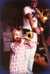 Ellekari, a 4-year-old child, learns how to breathe into a soprano trombone.